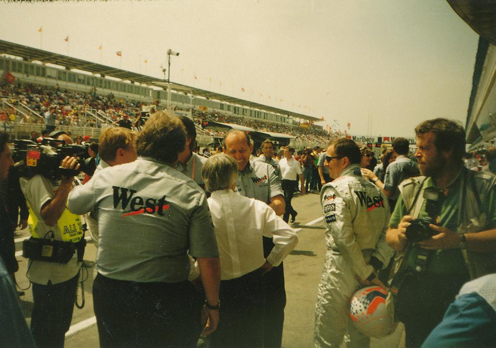 """Собственикът на Формула 1 Бърни Екълстоун (в гръб с бялата риза) поздравява шефа на """"Уест Макларън Мерцедес"""" Рон Денис с двойната победа. Вляво леко се вижда и Мика Хакинен. Снимка: Авторът."""